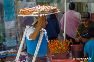 Man carrying a frame on shoulders and churros on his head