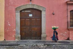 Woman in Antigua Guatemala carrying her snacks for sale on her head