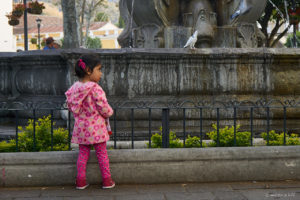 Little girl in Antigua`s center square watching the birds