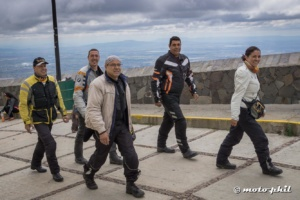 Group of motorcycle riders walking up to Cristo Rey statue