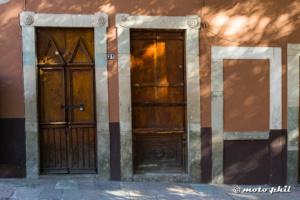 Wooden doors on brown and orange wall