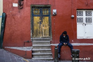 Old door in a red wall with a young guy sitting in front and texting