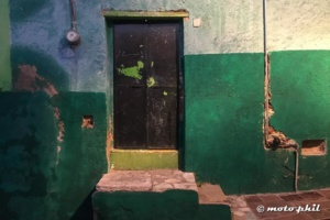 Dark brown door with green spots surrounded by green walls