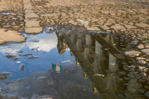 Reflection of colonial building and guatemalan flag in a puddle