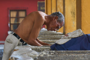 An old man using Tanque La Union to fresh up