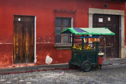 Lonely fruit stand in Antigua in front of red wall and wooden doors